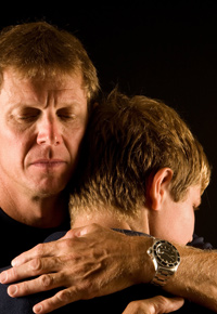 father reassuring teen son