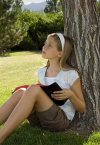 young girl by tree reading bible
