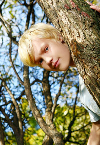boy behind tree