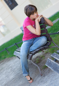 teen girl sitting on park bench contemplating