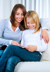 mom and daughter looking through magazine