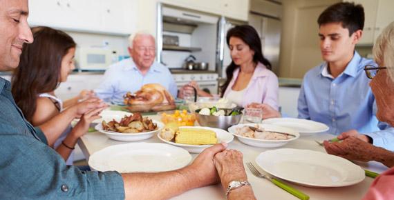 extended family praying at dinner table