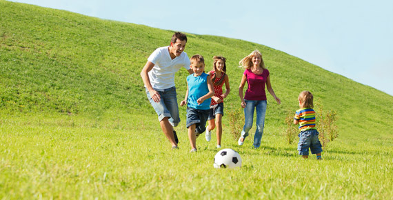 family playing soccer in field